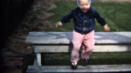 sinematografi : 8mm Vintage 1952 Extreme Girl Jumping Off Picnic Table Stok Video