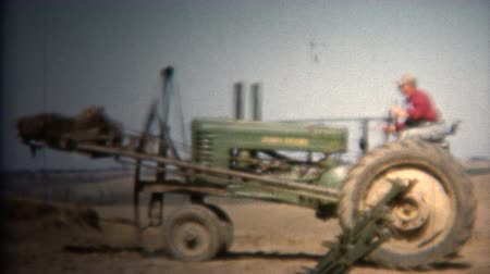 iowa : 8mm Vintage 1952 Farmer Moving Topsoil John Deere Tractor. Iowa, USA.