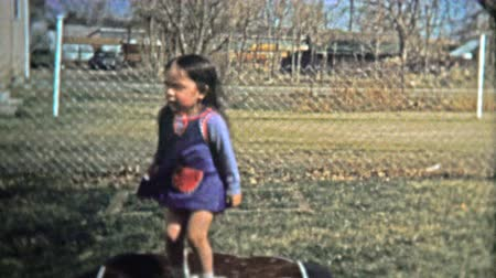 семидесятые годы : BOULDER, CO. USA - 1974: Girl practicing her jumping on small inflatable trampoline. Unique vintage 8mm film home movie professionally cleaned and captured in 4k 3840x2160 UHD resolution plus post processing including cinematic retro color correction, man