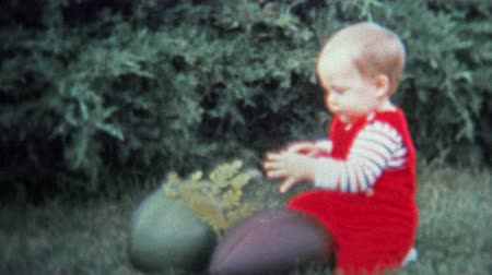 demokratický : DALLAS, TX - 1971: Parents put on military combat helmet for dress up day for baby. Unique vintage 8mm film home movie professionally cleaned and captured in 4k 3840x2160 UHD resolution plus post processing including cinematic retro color correction, manu