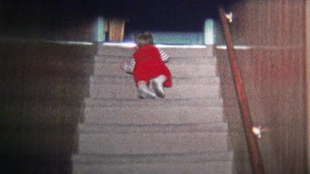 семидесятые годы : BOULDER, CO. USA - 1973: Babys momentous first climb up staircase. Unique vintage 8mm film home movie professionally cleaned and captured in 4k 3840x2160 UHD resolution plus post processing including cinematic retro color correction, manual speed adjustm