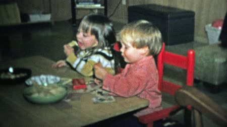 archívum : BOULDER, CO. USA - 1973: Siblings eating snack food in the romper-room dining table. Unique vintage 8mm film home movie professionally cleaned and captured in 4k 3840x2160 UHD resolution plus post processing including cinematic retro color correction, man Stock mozgókép