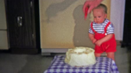 травма : BOULDER, CO. USA - 1973: One year old awkwardly walks to birthday party cake and burns himself on candle. Unique vintage 8mm film home movie professionally cleaned and captured in 4k 3840x2160 UHD resolution plus post processing including cinematic retro