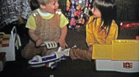 семидесятые годы : BOULDER, CO. USA - 1973: Brother mad at sister for grabbing at his new Christmas toy. Unique vintage 8mm film home movie professionally cleaned and captured in 4k 3840x2160 UHD resolution plus post processing including cinematic retro color correction, ma