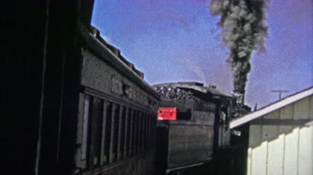 семидесятые годы : CUMBRES PASS, CO. - USA1972: Polluting old coal firing train pulling out of the station. Unique vintage 8mm film home movie professionally cleaned and captured in 4k 3840x2160 UHD resolution plus post processing including cinematic retro color correction, Стоковые видеозаписи