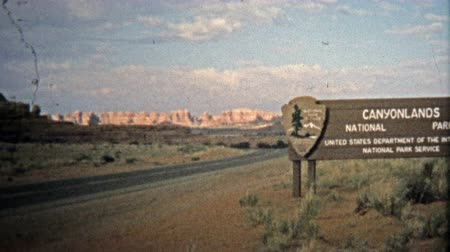 valóság : CANYONLANDS, UTAH -1971: Entering Canyonlands National Park with spectacular rock formations. Unique vintage 8mm film home movie professionally cleaned and captured in 4k 3840x2160 UHD resolution plus post processing including cinematic retro color correc Stock mozgókép