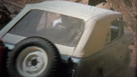 семидесятые годы : CANYONLANDS, UTAH -1971: Jeep climbing hills at Elephant Hill off-road track.  Unique vintage 8mm film home movie professionally cleaned and captured in 4k 3840x2160 UHD resolution plus post processing including cinematic retro color correction, manual sp Стоковые видеозаписи