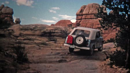 семидесятые годы : CANYONLANDS, UTAH -1971: Jeep driver bouldering up a steep incline offroad trail.  Unique vintage 8mm film home movie professionally cleaned and captured in 4k 3840x2160 UHD resolution plus post processing including cinematic retro color correction, manua