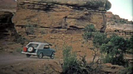 семидесятые годы : CANYONLANDS, UTAH -1971: Jeep driving to across the unique barren landscape. Unique vintage 8mm film home movie professionally cleaned and captured in 4k 3840x2160 UHD resolution plus post processing including cinematic retro color correction, manual spee Стоковые видеозаписи