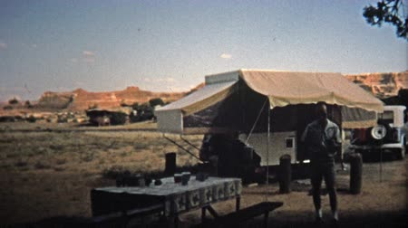 трейлер : CANYONLANDS, UTAH -1971: Popup trailer camping in the mesa wastelands.  Unique vintage 8mm film home movie professionally cleaned and captured in 4k 3840x2160 UHD resolution plus post processing including cinematic retro color correction, manual speed adj Стоковые видеозаписи