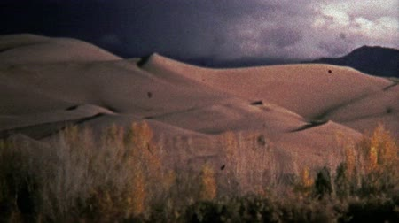 archívum : SAN LUIS VALLEY, CO. USA -1972: Great Sand Dunes National Park showcases glowing sand. Unique vintage 8mm film home movie professionally cleaned and captured in 4k 3840x2160 UHD resolution plus post processing including cinematic retro color correction, m