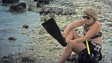 valóság : 1973: Women putting on snorkeling gear and swimming into the waves.
