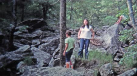 GREENSBORO, NC -1971: Girls playing around and hiking rocky boulder trail. Stok Video