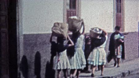 MEXICO CITY -1974: Local townspeople carrying things on their heads.