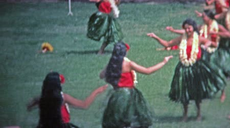 ostrovy : HAWAII 1976: Hawaii sign grass skirt hula dancers show off to crowds.