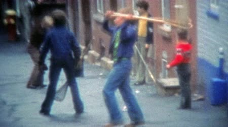 archívum : MONTREAL, CANADA 1975: Urban thug Canadian children playing street ball with lacrosse nets. Stock mozgókép