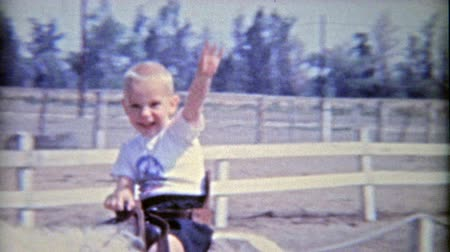 1962: Boys riding horses for 1st time smile and wave hello.