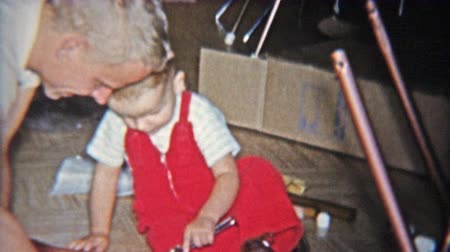 1962: Dad and toddler son building toy rocking horse together from box kit. Wideo