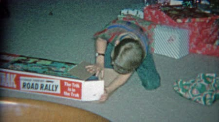 1963: Kid unwrapping road rage electric slot car racer toy for Christmas gift.