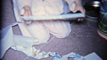 1963: Child opening a religious hymns psalms church book for Christmas gift. Wideo