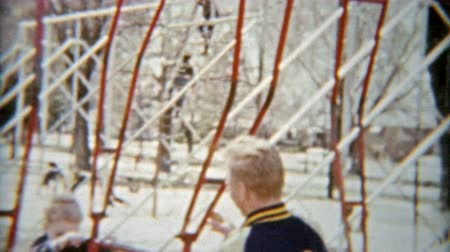 1964: Boy and dad swinging on playground toys and smiling hard. Wideo