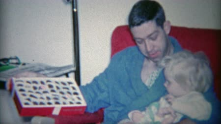 korszak : 1964: Dad showing child box of chocolates in comfortable morning robe fashion.