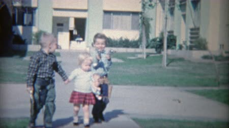 1964: Armed children with toy guns holstered shooting and laughing.
