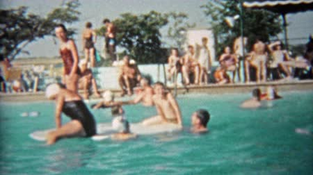 all ages : 1959: People of all ages playing in public pool during a hot summer day.