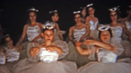 1957: White ballet dance dressed group performance of adults and children.