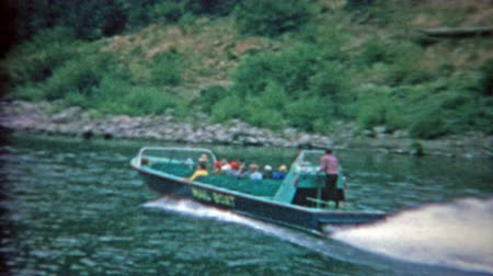 1957: Mail boat taking tourists up river sightseeing and dropping postage along the way. Stok Video