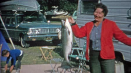 kano : 1966: Women catches big lake trout fish at trailer park campsite has trouble holding it.