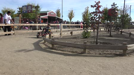 Little kids small pedal car racers at local fall fest western celebration amusement fair.