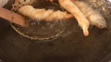 short clip : Taking deep-fried prawns out of fat with a skimmer Stock Footage