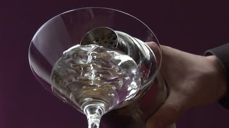 garniture : Pouring Martini from shaker into glass & garnishing with olive Stock Footage