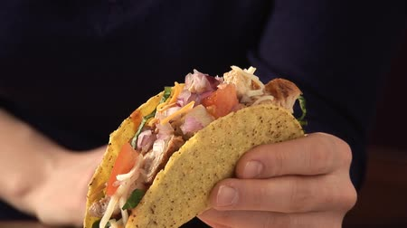 kökenleri : Hand holding taco shell filled with chicken