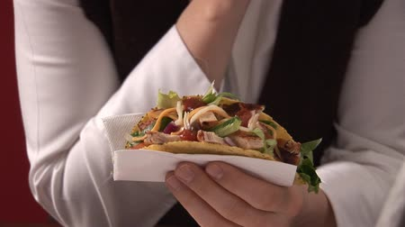 poulet : Woman holding taco shell filled with chicken in paper napkin