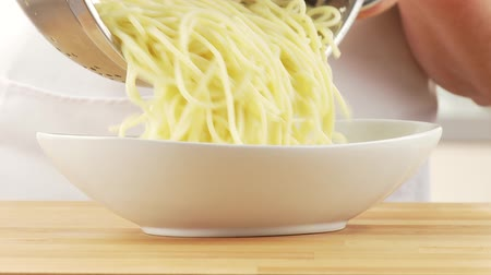spagetti : Drained spaghetti being placed in a bowl