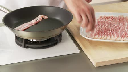 frypan : Rashers of bacon being placed in a pan