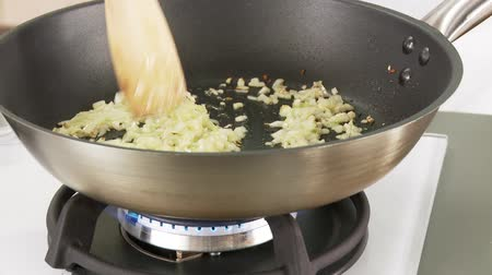 Onion and garlic being fried in a pan