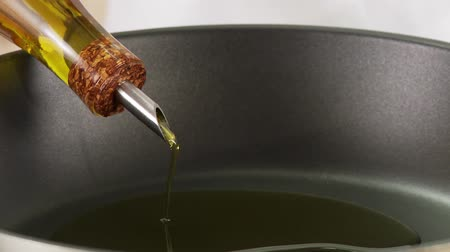 poured out : Olive oil being added to a pan