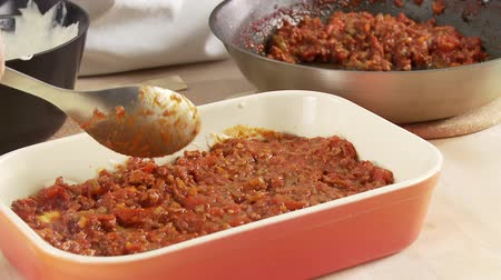short clip : Minced meat sauce and lasagne sheets being layered in a baking dish