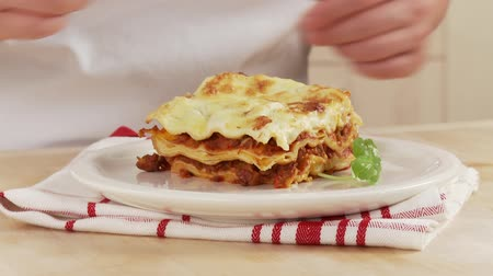 garniture : A piece of lasagne being garnished with basil Stock Footage