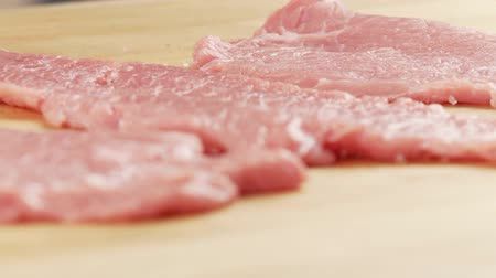 common salt : Tenderised veal escalopes being turned and seasoned with salt and pepper