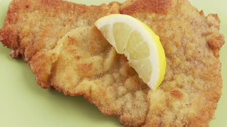 garniture : Escalope á la viennoise being garnished with a slice of lemon and a sprig of parsley Stock Footage