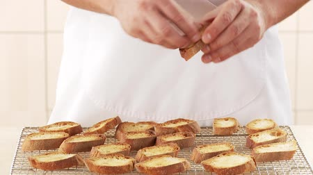 crostini : Toasted baguette slices being rubbed with garlic