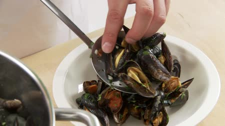 plating food : Cooked mussels being arranged on a deep plate