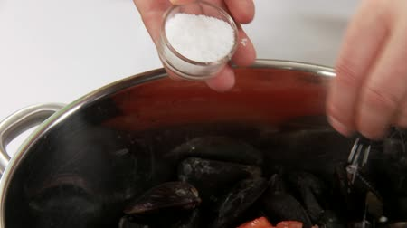 common salt : Tomato pieces being added to mussels and salted Stock Footage