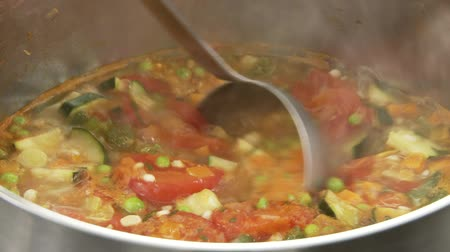 buharlama : Minestrone being scooped out of a pot with a ladle Stok Video