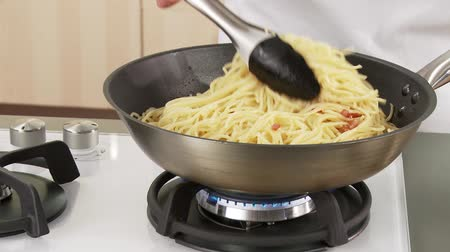 basic steps : Spaghetti being added to fried bacon Stock Footage