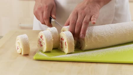 creams : Strawberry cream swiss roll being sliced
